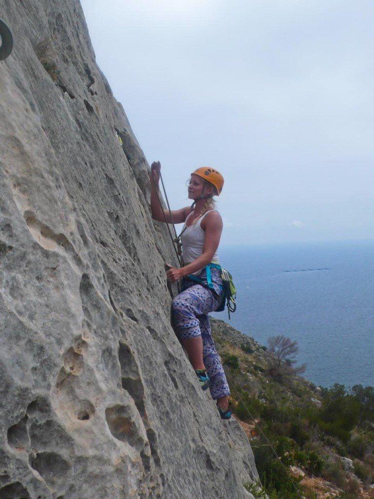 Woman lead climbing in Spain with view to the seaside